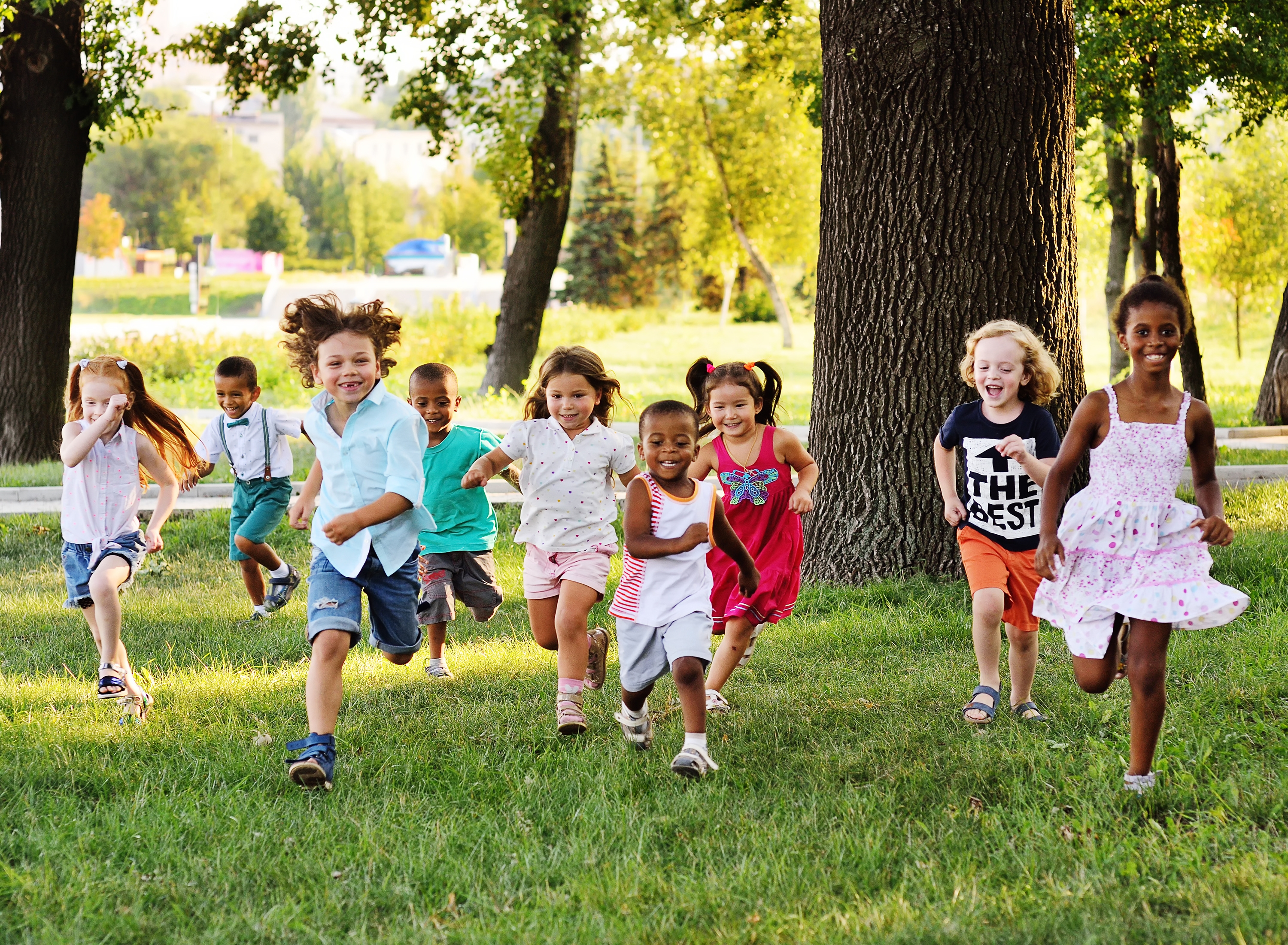 a group of preschoolers running on the grass in the Park.